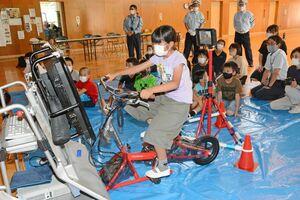 自転車シミュレーターに乗り、運転する児童=嬉野市嬉野町の大野原小中学校