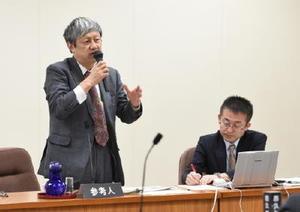 フリーゲージトレインの不具合対策など今後の進展について話す潮崎俊也審議官(左)=県議会