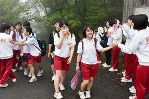 生徒会の役員たちに励まされ、疲れを吹き飛ばすように笑顔を見せる生徒たち=小城市の天山山頂付近