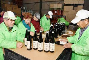 出来上がった日本酒に1本ずつ丁寧にラベルを貼る参加者=みやき町の天吹酒造