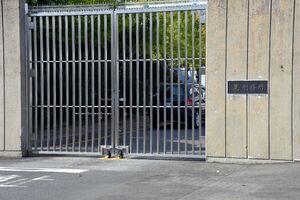 麓刑務所の正門。高いコンクリートの壁と鉄格子の向こうに管理棟や居室棟などがある=鳥栖市山浦町