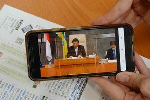 スマートフォンに映し出された佐賀市議会本会議の動画