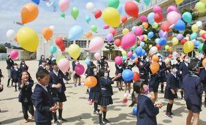 「仲良しの種」を付けた風船を一斉に大空へ飛ばす児童たち=唐津市浜玉町の平原小