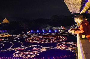 物見やぐらから写真を撮る来園者たち=神埼市郡の吉野ケ里歴史公園