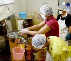 ミカンジュースの製造を体験する生徒たち。太良町名産のフレッシュなみかんを、自分たちの手で機械に投入する