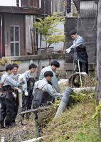草を刈ったり、空き缶を拾ったりする佐電工の新入社員たち=佐賀市天神のクリーク