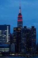 緊急医療従事者をたたえ、赤と白にライトアップされたエンパイアステートビル=3月3月31日、米ニューヨーク(AP=共同)