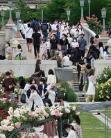 大阪市内の公園を歩くマスク姿の人たち=15日午後