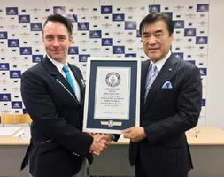 ギネスの記録員から認定書をもらう澤田秀雄社長(右)=東京都内
