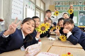 完成した布製のヒマワリを手に、笑顔を見せる子どもたち=上峰小学校