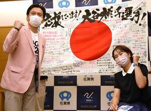 県民からのメッセージが書かれた旗を前に記念撮影する山口祥義知事(左)と大谷桃子選手=佐賀県庁