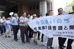 「手話はいのち」と書かれた横断幕を持ちパレードした聴覚障害者や支援者たち=佐賀県議会