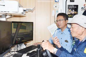 「ドライブシミュレーター」で、飛び出しなどに注意して運転体験する参加者=佐賀市の北川副公民館