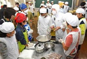 マイスターの萩原隆文さん(手前の右から4人目)と一緒にようかんを作る児童たち=基山町の若基小学校