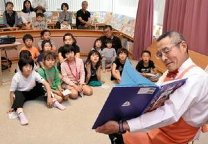 鹿島市生涯学習センター「エイブル」の開館15周年を記念した催しで、子どもたちに絵本の読み聞かせをするお父さん=鹿島市民図書館