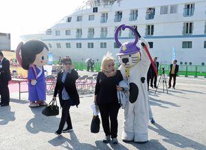 唐津港に初めて入港したクルーズ船「スター・レジェンド」から降り、ご当地ゆるキャラ「唐ワンくん」の歓迎を受ける外国人客=唐津市の唐津東港