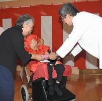 還暦お祝い会で記念品と花束を受け取った中村正子さん(中央)と母の陽子さん(左)