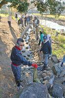砂利や石が敷き詰められた水路に水が流れ、感慨にふける参加者たち=佐賀市の県立森林公園