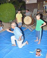 地域のお年寄りに大太鼓の所作を習う子どもたち=基山町の西長野地区にある天満宮