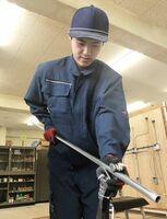 工具のベンダを使い、金属管を曲げる高祖拓実さん=佐賀市の佐賀工業高