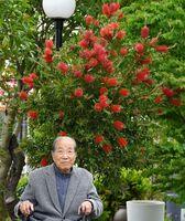 鮮やかに色づいたブラシノキの前で笑顔を見せる秋吉五郎さん=みやき町原古賀