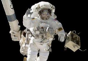 2012年9月の船外活動で、ロボットアームに乗って宇宙空間を移動する星出彰彦さん(NASA提供・共同)