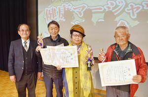 県麻雀段位審査会の吉田和英会長(左)と上位入賞者ら=佐賀市白山のエスプラッツホール