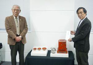 11代斎藤用之助が持ち帰った琉球国王ゆかりの盃など(中央)を沖縄県立博物館・美術館に寄贈した14代用之助さん(左)。右は田名真之館長=8日午後、那覇市