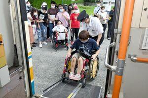 運転士の補助で副島愛佳さんがバスを降りる様子を見守る佐賀女子短大の学生ら=佐賀市