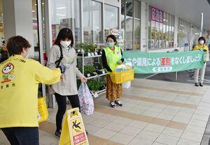 買い物客にチラシやグッズを配り、人権への配慮を呼び掛ける関係者=佐賀市与賀町のゆめマートさが