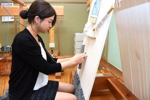鍋島緞通を織る吉島夕莉子さん=佐賀市大和町の無寒暑庵
