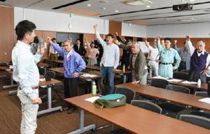 長崎地裁の判決が出るのを前に、開門を求めて気勢を上げる参加者=佐賀市の県弁護士会館