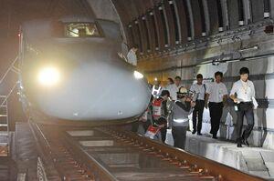 線路上で停車した新幹線内から降車して避難する訓練参加者ら=27日未明、筑紫トンネル付近