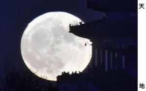 北京で観測された「スーパームーン」。いつもより大きく見える満月が、公園に集まった人たちを照らした=14日午後5時29分(共同)