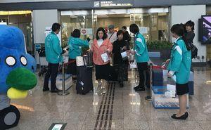 佐賀空港に到着し、記念品を受け取る搭乗客=佐賀市川副町の佐賀空港(県提供)