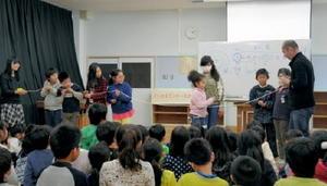ロープを使って太陽系の惑星の位置関係を児童に説明する高梨直紘さん(右)=唐津市の長松小学校
