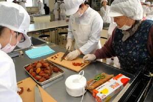 地域おこしグループメンバーの指導を受けながら巻き柿作りに挑戦する学生=佐賀市の佐賀女子短大