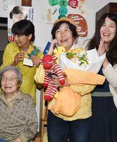 当選が確実となり、祝福の電話を受けて笑顔を見せる山下明子さん(中央)=15日午後11時12分、佐賀市中の小路の事務所