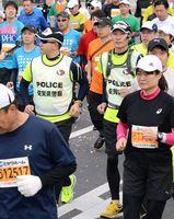 ランナーを見守りながら走るランニングポリス=佐賀市の県総合運動場前