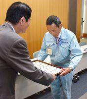 市教委の東島正明教育長から感謝状を贈られる岩本重男さん=佐賀市の市立図書館
