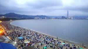 午後7時半、砂浜に陣取り、開始を待つ人たち=西の浜