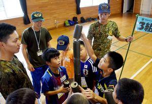 空き缶を高く積み上げる子どもたちと見守る自衛隊員=吉野ヶ里町の陸上自衛隊目達原駐屯地
