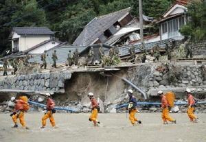 行方不明者の捜索活動を終え、濁流を渡って引き揚げる消防隊員と自衛隊員=10日午後、福岡県朝倉市