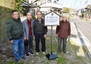 旧道に表示板を設置した楠久・津まちづくり実行委員会のメンバー=伊万里市山代町