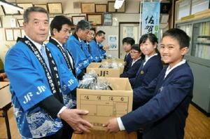 県有明海漁協の竹下元一副組合長(左)らから佐賀海苔を受け取る子どもたち=みやき町の中原小学校