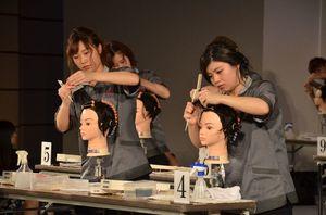 髪にパーマをかける「ワインディング」の競技に挑戦する学生たち=佐賀市文化会館