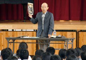 事故で亡くなった息子の写真を手に、命の大切さを訴える高濵伸一さん=佐賀市の佐賀大付属中