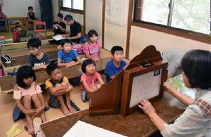 紙芝居に見入る北方町医王寺地区の子どもたち=武雄市北方町の医王寺公民館
