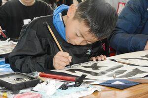 清書した作品に真剣な表情で名前を書き入れる参加者=神埼市の王仁博士顕彰公園