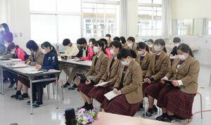 大和青藍高(福岡県)の生徒の発表をメモを取りながら真剣に聞く神埼清明高の生徒ら=神埼市の同高